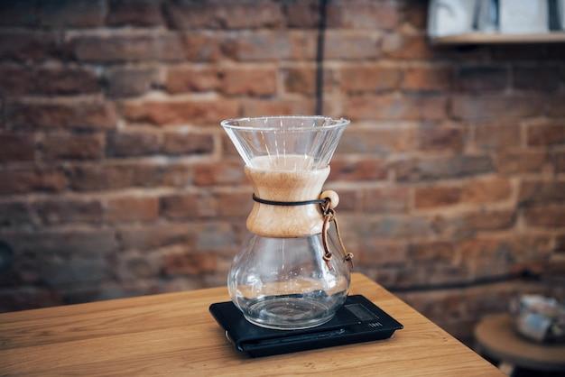 Rocznika ekspres do kawy kolba na drewnianym stole w sklep z kawą