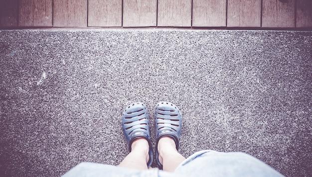 Rocznika filtr: widok z lotu ptaka szarość but z błękitnym cajgu stojakiem na betonie i drewnianej desce