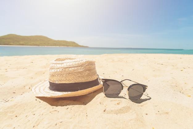 Rocznika kapelusz i okulary przeciwsłoneczni na plażowej pięknej piasek plaży jako lato