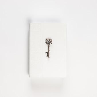 Rocznika klucz na białej książce na bielu