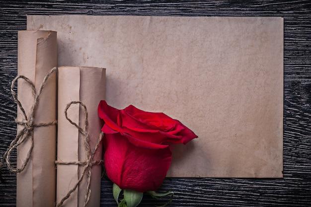 Rocznika papier stacza się czerwonego aromatycznego rosebud na drewnianym tle