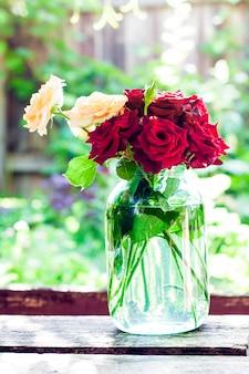 Rocznika różany bukiet w szklanym słoju na zamazanej zieleni ogródu tle