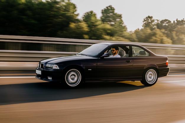 Rocznika sedanu samochodowy jeżdżenie na autostradzie. widok z boku.