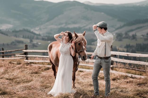 Rocznika ślubu państwo młodzi na rancho z koniem na szczytowych wzgórzach