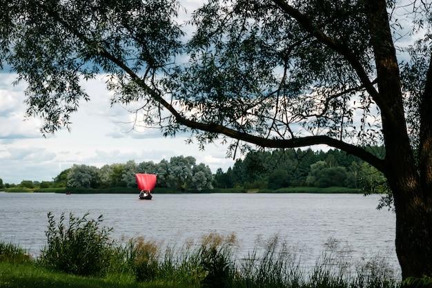 Rocznika statku łódź z czerwonym żaglem na rzece