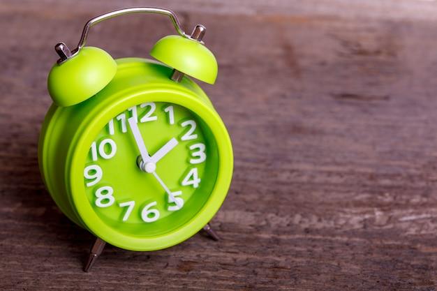 Rocznika zielony retro budzik na drewno stole z pustą przestrzenią dla twój teksta. klasyczny z podwójnym dzwonkiem.