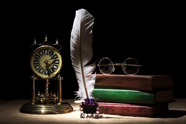 Roczników retro szkła na starych książkach zbliżają kałamarz z piórkiem i starym zegarem przeciw czarnemu tłu