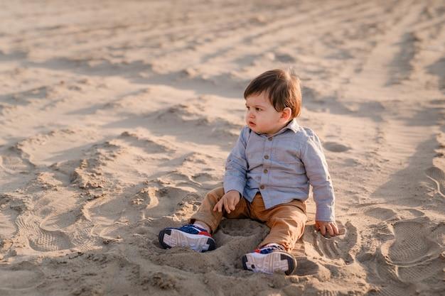Roczny chłopiec siedzi na piasku, uśmiecha się i bawi.