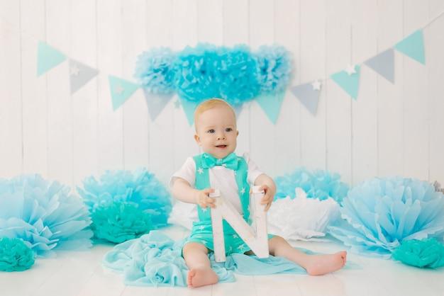 Roczny chłopiec świętuje swoje pierwsze urodziny, trzyma literę n w dłoniach i uśmiecha się