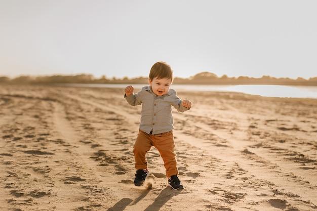 Roczny chłopiec uczy się chodzić po piasku nad rzeką.