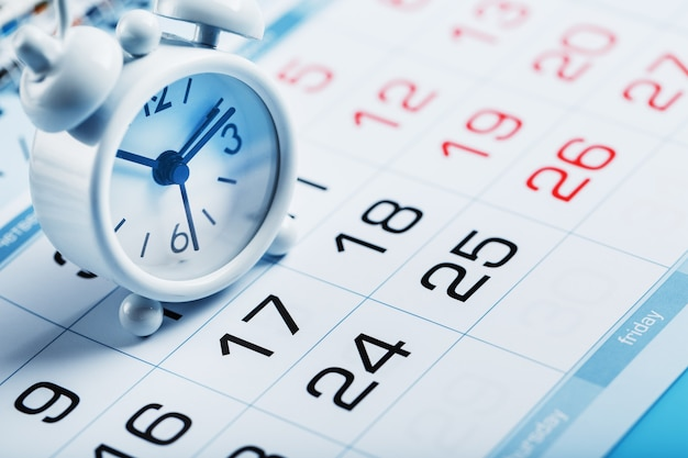 Roczny kalendarz z białym budzikiem na niebieskim tle
