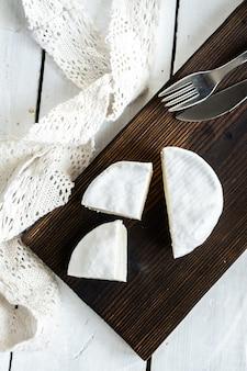 Rodzaj sera brie. ser camembert. świeży ser brie i plasterek na drewnianej desce. włoski