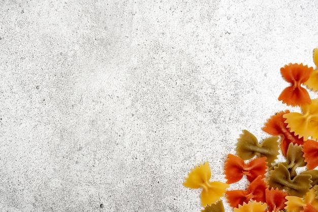 Rodzaje niegotowanego makaronu. farfalle zielony, żółty i czerwony makaron suszy się na jasnym tle betonu. leżał płasko, widok z góry, miejsce