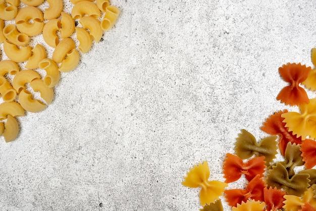 Rodzaje niegotowanego makaronu. makaron chifferi i farfalle zielony, żółty i czerwony suchy na jasnym tle betonu. leżał płasko, widok z góry, miejsce