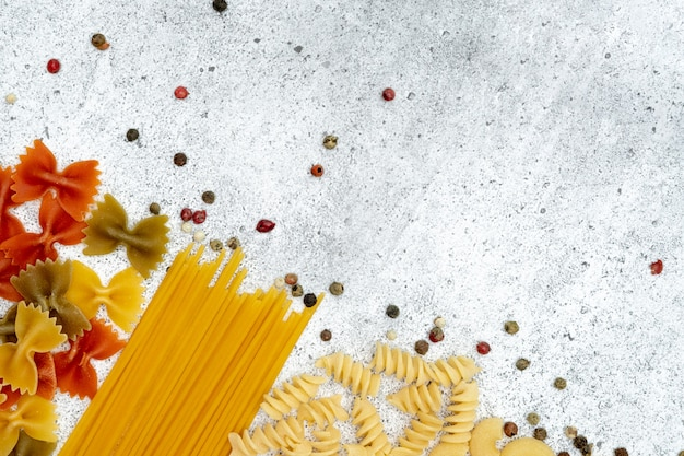 Rodzaje niegotowanego makaronu. makaron fusilli, farfalle, spaghetti, chifferi i kolorowy groszek suszone na jasnym tle betonu. . leżał z płaskim, widok z góry, miejsce