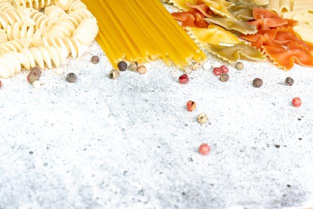 Rodzaje niegotowanego makaronu. makaron penne, fusilli, farfalle, niegotowane spaghetti na jasnym tle betonu. leżał płasko, lato
