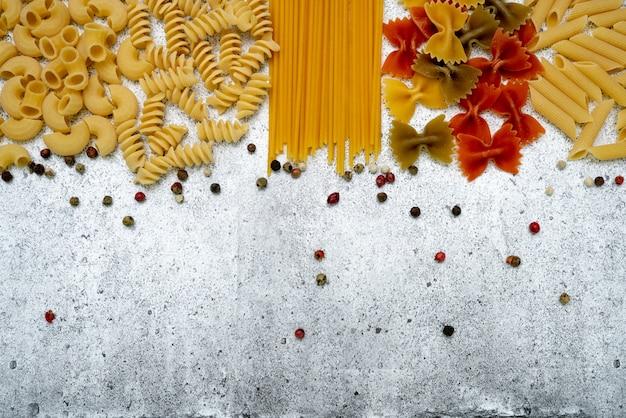 Rodzaje niegotowanego makaronu. makaron penne, fusilli, farfalle, spaghetti, chifferi i kolorowy groszek wytrawne na jasnym tle betonowym. leżał płasko, widok z góry, miejsce