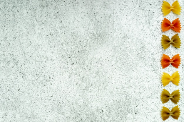 Rodzaje niegotowanego makaronu na betonowym tle