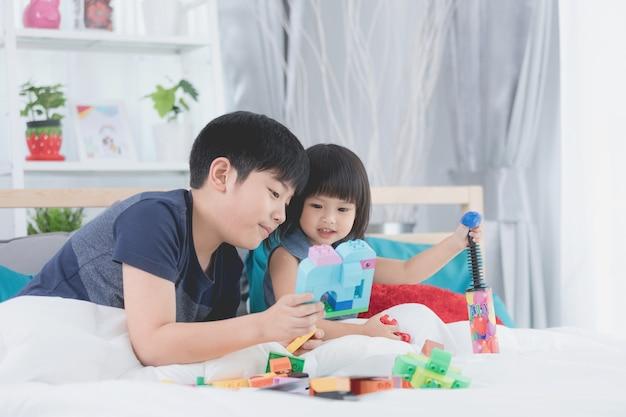 Rodzeństwo azjatyckich dzieci, brat i siostra grające w bloku konstruktora,