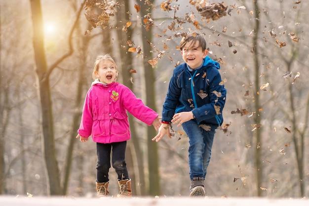 Rodzeństwo dzieci bawiące się liśćmi klonu w jesiennym parku