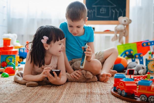 Rodzeństwo dzieci brat i siostra, przyjaciele siedzą na podłodze domu w pokoju zabaw dla dzieci ze smartfonami, oderwanymi od rozrzuconych zabawek.