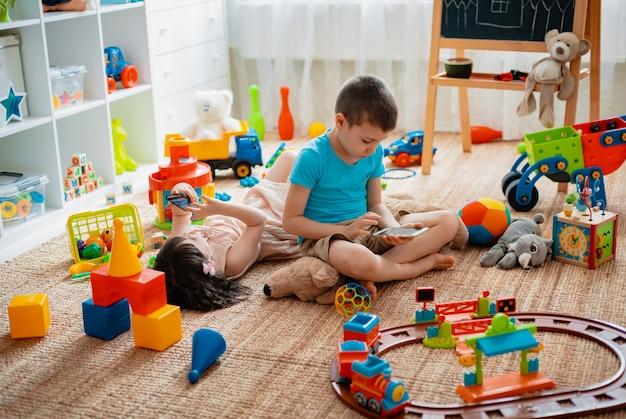 Rodzeństwo dzieci brat i siostra, przyjaciele siedzą na podłodze w pokoju zabaw dla dzieci w domu ze smartfonami, oderwanymi od rozrzuconych zabawek.