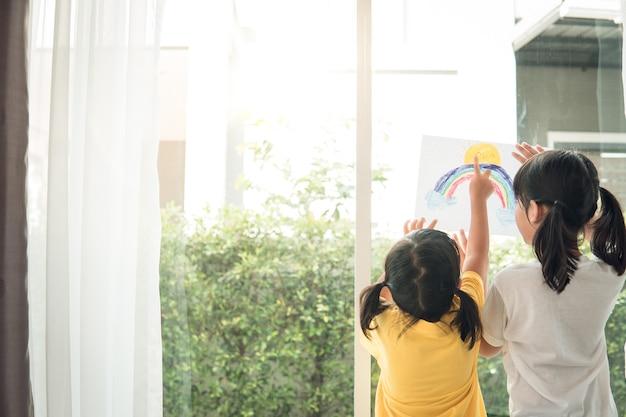 Rodzeństwo dziewczynka rysująca tęczę wygląda przez okno podczas kwarantanny covid19 zostaje w domu