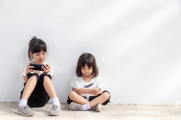 Rodzeństwo dziewczynki oglądające swoje smartfony na białym tle społeczna koncepcja o nowej technologii