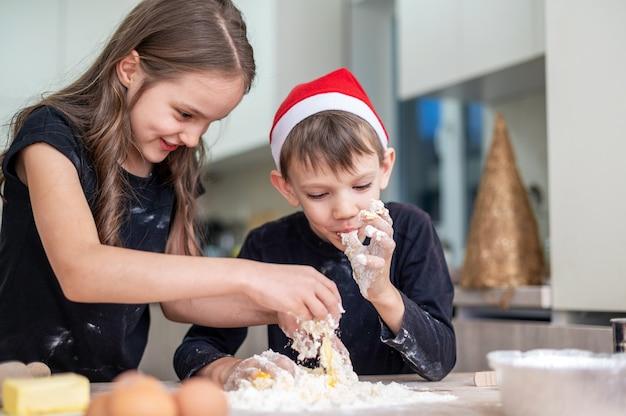 Rodzeństwo gotuje i wygłupia się w kuchni, chłopiec w świątecznej czapce. pomysł na szczęśliwe dzieci