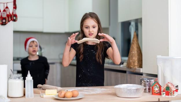Rodzeństwo gotuje na kuchni, chłopiec w świątecznej czapce, dziewczynka wymiotuje ciasto. pomysł na szczęśliwe dzieci