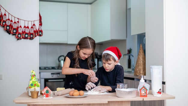 Rodzeństwo gotuje w kuchni, chłopiec w świątecznej czapce. pomysł na szczęśliwe dzieci