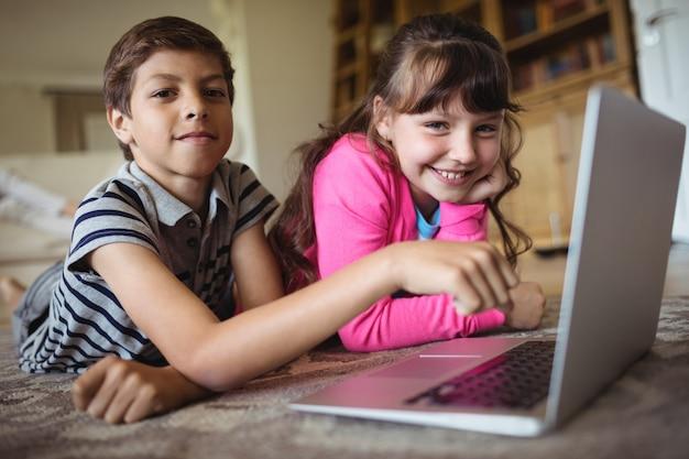 Rodzeństwo korzysta z laptopa w salonie