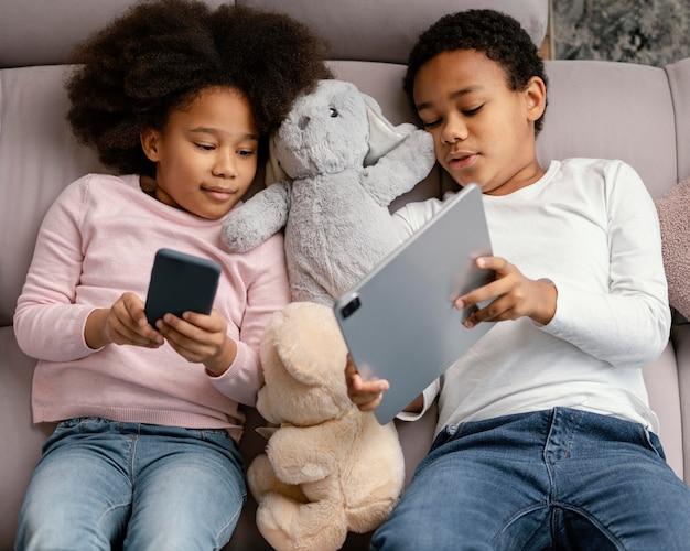 Rodzeństwo korzystające z tabletu i telefonu komórkowego w domu