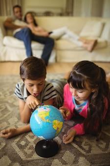 Rodzeństwo leżące i patrząc na świecie w salonie