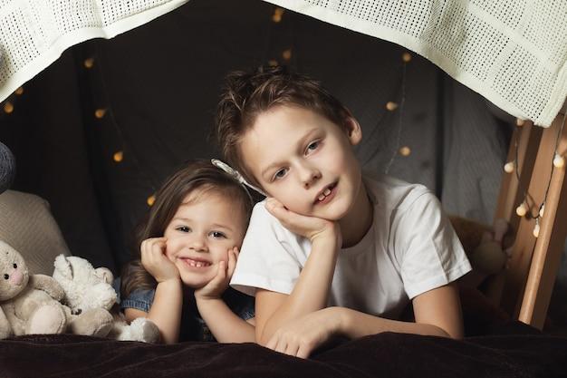 Rodzeństwo leży w chatce z krzesłami i kocami. brat i siostra uśmiechają się, bawią się w domu