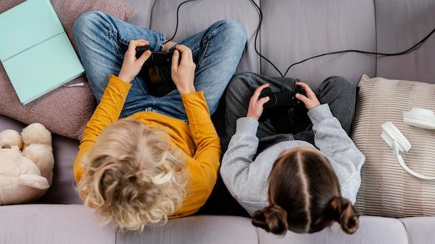 Rodzeństwo na kanapie z joystickami grającymi