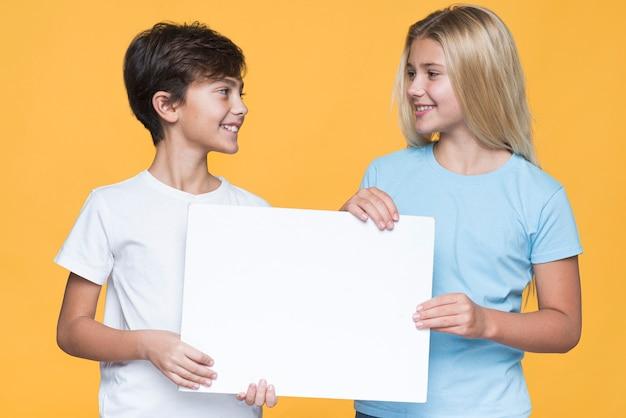 Rodzeństwo, patrząc na siebie, trzymając arkusz papieru