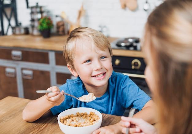 Rodzeństwo patrzy na siebie podczas jedzenia