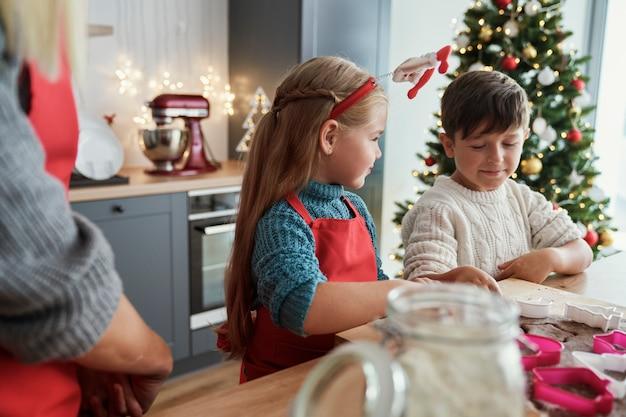 Rodzeństwo piecze pierniki w domowej kuchni