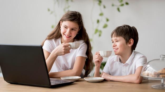 Rodzeństwo pije herbatę i korzysta z laptopa
