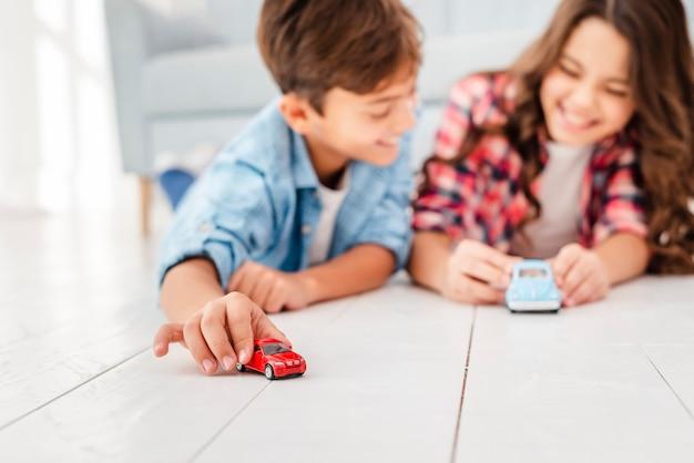 Rodzeństwo pod niskim kątem na podłodze bawi się zabawkami