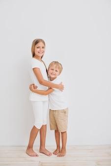 Rodzeństwo przytulanie, patrząc w kamerę