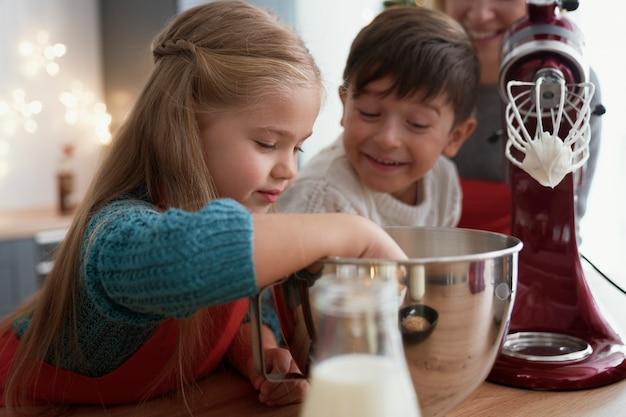 Rodzeństwo smakuje pastę cukrową podczas pieczenia z rodziną