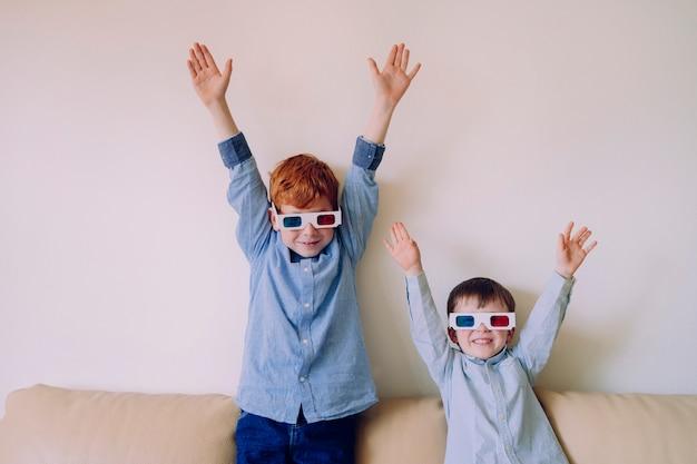 Rodzeństwo szczęśliwe na wakacje w domu. bracia w trójwymiarowych okularach bawią się i śmieją z kanapy.