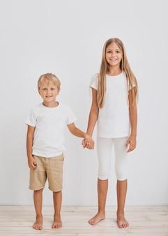 Rodzeństwo, trzymając się za ręce, patrząc w kamerę