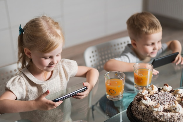 Rodzeństwo w domu grające na telefonie komórkowym