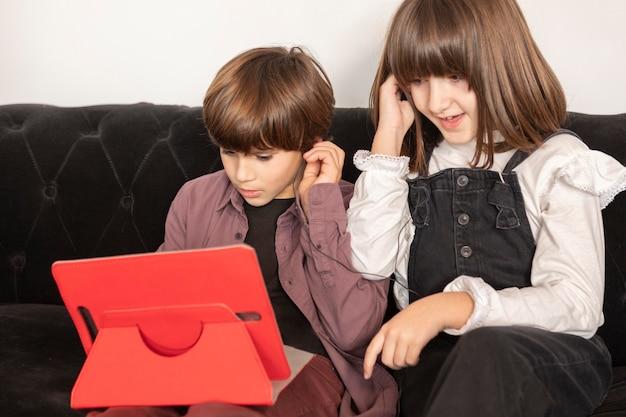 Rodzeństwo W Domu Za Pomocą Tabletu Premium Zdjęcia