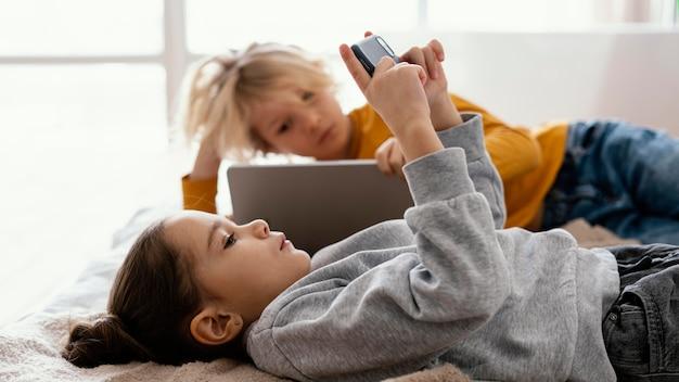 Rodzeństwo w łóżku grające na telefonie komórkowym i tablecie