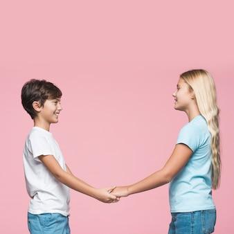 Rodzeństwo widok z boku, trzymając się za ręce