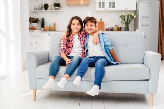 Rodzeństwo widok z przodu przytulanie na kanapie